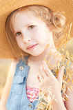Cute kid girl outdoors. Smiling little girl holding dry grass, wearing straw outdoors Royalty Free Stock Images
