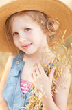 Cute kid girl outdoors. Smiling little girl holding dry grass, wearing straw outdoors Royalty Free Stock Photography
