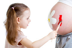 Cute kid girl painting mother's belly Royalty Free Stock Photo