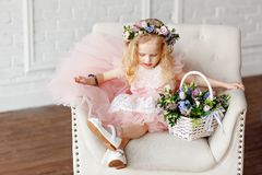 A cute kid - girl in a in a pink dress and flower crown. Beautiful little girl in a bright studio sits, lauht and looks royalty free stock photos
