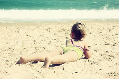 Cute kid (girl) playing at the beach. toned image Royalty Free Stock Photo