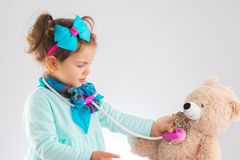 Cute kid girl playing doctor with medical headphones and her plush toy at home Royalty Free Stock Photo