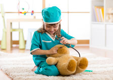 Cute kid girl playing doctor with plush toy at home Stock Photos