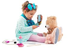Cute kid girl playing doctor with plush toy at home Stock Images
