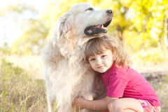 Cute kid girl playing with dog outdoors Royalty Free Stock Images