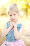 Cute kid girl posing on nature background. Closeup portrait of cute baby girl on nature background outdoors Royalty Free Stock Image