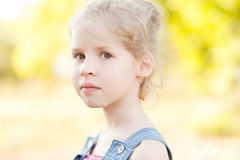 Cute kid girl posing on nature background. Closeup portrait of cute baby girl on nature background outdoors Royalty Free Stock Images