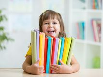 Cute kid girl preschooler with books indoor Stock Image