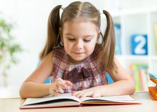 Cute kid girl reading story from big book in Stock Photos