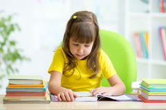 Cute kid girl reading story from book in nursery Royalty Free Stock Photo