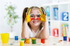 Cute kid girl showing her hands painted in bright. Cute cheerful kid girl showing her hands painted in bright colors royalty free stock photography
