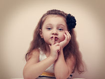 Cute kid girl showing silence sign the finger near lips. Vintage Stock Photography