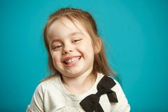 Cute kid girl with a snide smile and low-key laughter stands on blue isolated background. royalty free stock photo