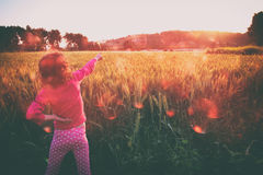 Cute kid (girl) standing in field at sunset with hands stretched looking at the landscape. instagram style image with bokeh lights. Freedom and happiness stock photos