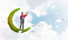 Concept of careless happy childhood with girl on green moon Royalty Free Stock Images