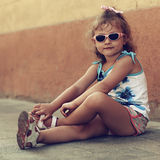 Cute kid girl in sun glasses sitting on road in town Stock Images