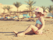 Cute kid girl sunbathing on beach Royalty Free Stock Images