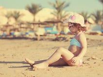 Cute kid girl sunbathing on beach Royalty Free Stock Images