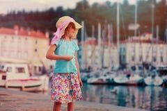 Cute kid girl walking on coastline in Piran, Slovenia on summer vacation Stock Photos