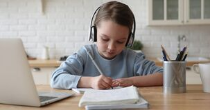 Cute kid girl wearing headphones studying at home writing notes
