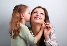 Cute kid girl whispering the secret to her toothy laughing looki Royalty Free Stock Images