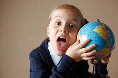 Cute kid with globe showing tongue. Little girl with a globe showing tongue stock photography