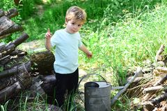 Cute kid has idea about something. Big watering pot is in front of little boy surrounded by grass. Young child wants to royalty free stock image