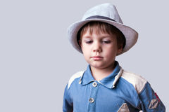 Cute kid with hat looking down. Cute unhappy kid with hat looking down Royalty Free Stock Images