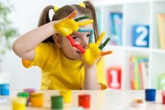 Cute kid have fun painting her hands. Cute kid girl have fun painting her hands Royalty Free Stock Images