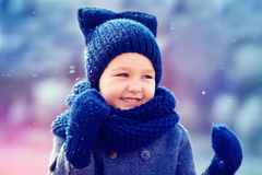 Cute kid having fun under the winter snow Stock Images