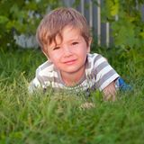 Cute kid having outside activities. Child on the grass. stock photos