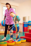 Cute kid having physical musculoskeletal therapy in rehabilitation center Stock Photography