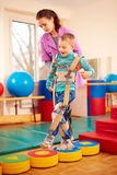 Cute kid having physical musculoskeletal therapy in rehabilitation center Royalty Free Stock Image