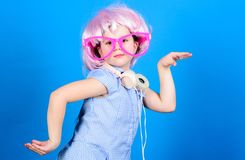 Cute kid with headphones blue background. Small girl headphones pink wig dancing. Child using technology for fun. Modern stock image