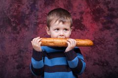 Little boy eating the french baguette. Cute kid holding and biting French bread against dark red background stock photography