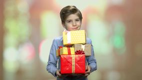Cute kid holding stack of gift boxes. Portrait of lovely boy with pile of gift boxes looking at camera. Birthday gifts concept stock footage