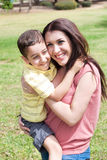 Cute kid hug is mom. In the park, outdoor Royalty Free Stock Photo