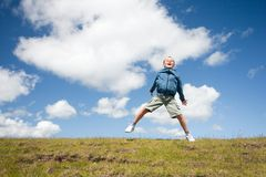 Cute kid jumping for joy. In the air in a beautiful landscape with blue sky and fluffy clouds Stock Photography