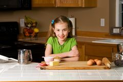 Cute kid in the kitchen. A pretty young girl ready to bake in a home kitchen Royalty Free Stock Photo