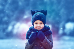 Cute kid in knitted wear and felted coat under winter snow Royalty Free Stock Image