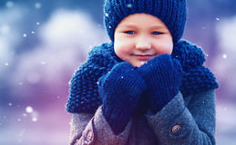 Cute kid in knitted wear and felted coat under winter snow Stock Images