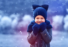 Cute kid in knitted wear and felted coat under winter snow Stock Image