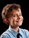Cute kid laughing. Studio portrait of a schoolboy laughing, isolated on dark background Royalty Free Stock Images