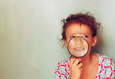 Cute kid looking through magnifying glass Royalty Free Stock Photos