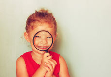 Cute kid looking through magnifying glass. Royalty Free Stock Photo