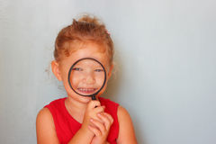 Cute kid looking through magnifying glass Royalty Free Stock Images