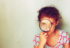 Cute kid looking through magnifying glass. Stock Photography