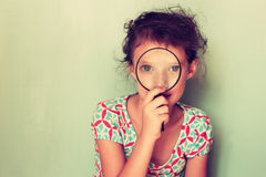 Cute kid looking through magnifying glass Stock Photo