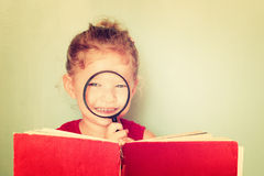 Cute kid looking through magnifying glass . Stock Photography