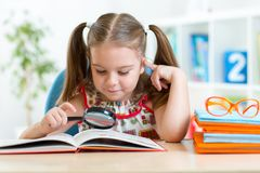 Cute kid looking through a magnifying glass with Stock Image